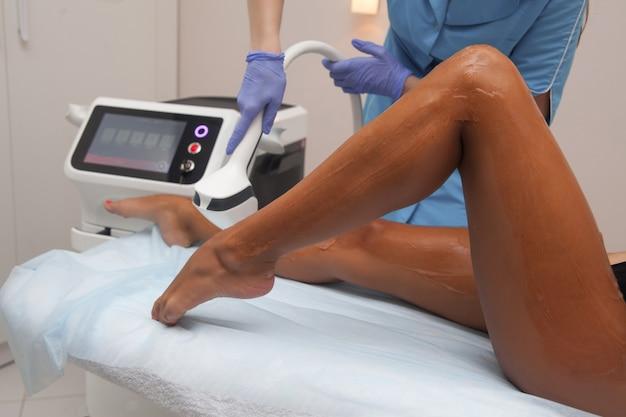 Épilation au laser et cosmétologie dans un salon de beauté. procédure d'épilation. concept d'épilation au laser, de cosmétologie, de spa et d'épilation. belle femme se faire épiler les jambes