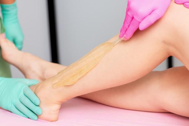Épilation au sucre liquide sur les jambes.