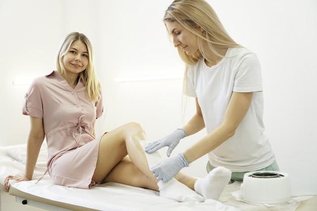 Épilation des belles jambes féminines. épilation à la cire dans un salon de beauté