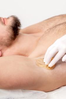 Epilation et épilation aisselle masculine avec pâte à sucre liquide. main de cosmétologue appliquant de la pâte de cire sur l'aisselle de l'homme. concept lisse sous les aisselles