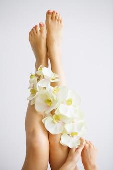 Épilation. gros plan femme mains touchant de longues jambes, peau douce