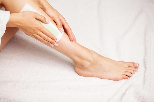 Épilation jambe de femme avec bande de cire au spa de beauté.