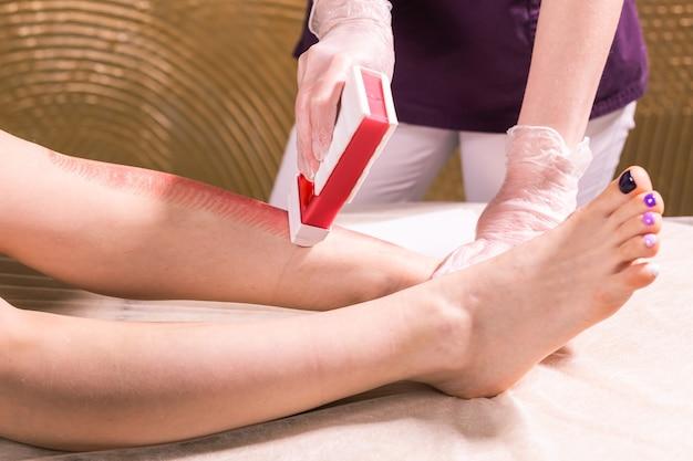 Épilation à la jambe de femme. procédure d'épilation d'esthéticienne à la cire de salon. épilation du corps féminin pour l'épilation par