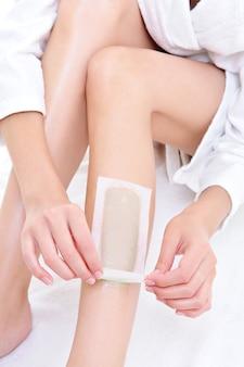 Épilation de la partie des jambes féminines avec épilation - espace blanc