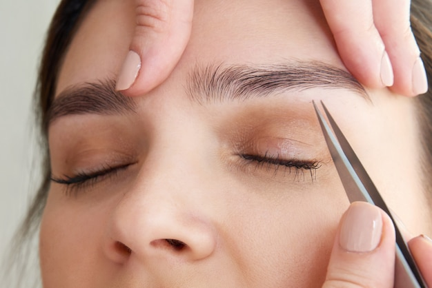 Épilation des sourcils féminins avec des pincettes pendant la correction des sourcils dans un salon de beauté