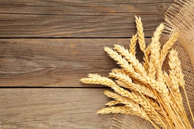 Épillets de blé avec un sac sur bois gris avec copie espace