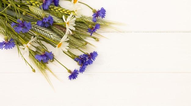 Épillets, bleuets et marguerites sur un fond en bois blanc. vue de dessus. espace de copie. bannière