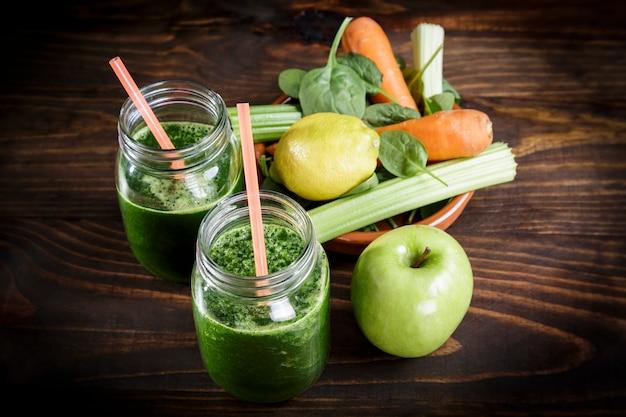 Épinards au jus de pomme et de légumes un pot de boisson gazeuse avec de la paille sur une table en bois