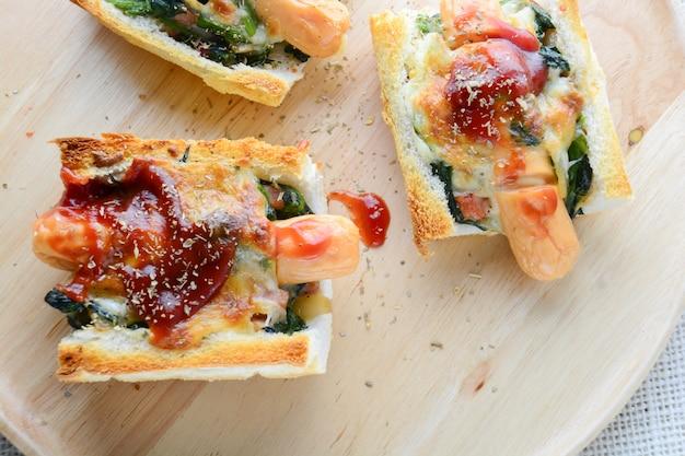 Épinards cuits au four avec fromage, saucisse sur baguette, pain français