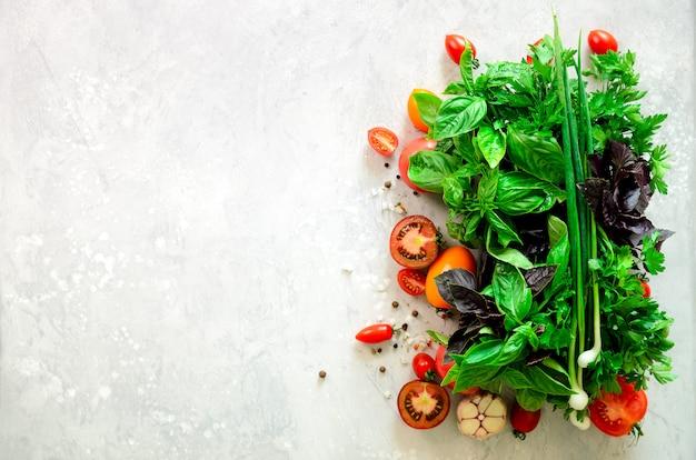 Épinards frais, oignons verts, basilic, herbes, aneth et tomates sur fond de béton gris, mise au point sélective.