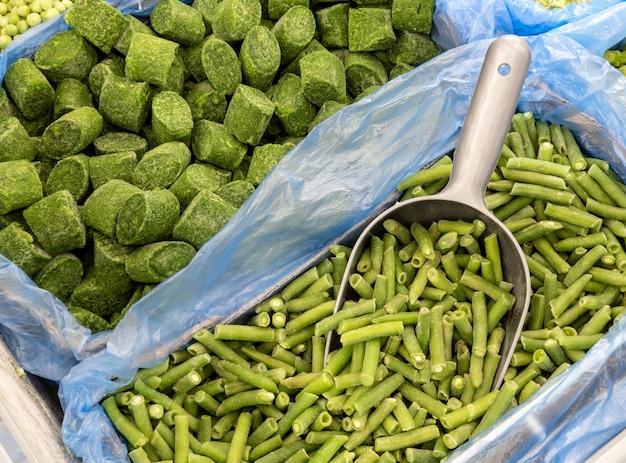 Épinards et haricots verts surgelés dans une boîte sur un comptoir de magasin