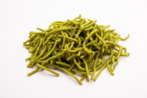 Les épinards ou palak sev sont des nouilles salées frites croustillantes. fait maison le shev ou le namkeen vert épais et mince est un en-cas indien classique. servi dans un bol ou une assiette