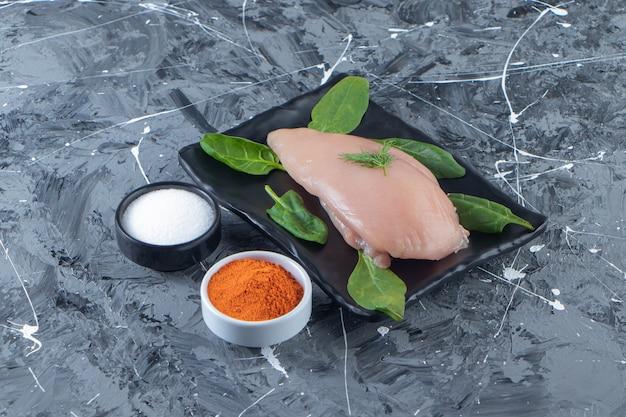 Épinards et poitrine de poulet sur un plateau à côté de bols d'épices et de sel, sur la surface en marbre.