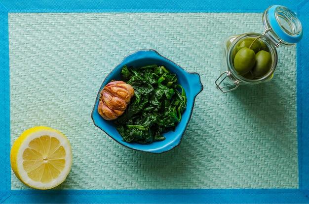 Épinards préparés dans un bol bleu avec ail, citron et olives sur fond bleu