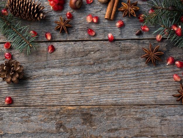 Épinettes de grenade branches anis étoilé, cannelle et épices d'hiver sur bois