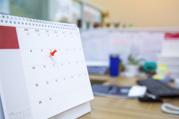 Une épingle de couleur rouge sur le calendrier, concept pour planificateur d'événements.
