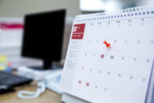 Une épingle de couleur rouge sur le concept de calendrier pour le planificateur d'événements.