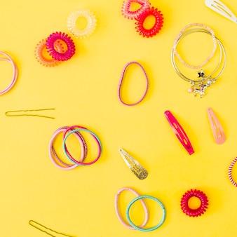 Épingles à cheveux et élastiques sur jaune