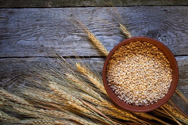 Épis de blé et un bol de blé sur une planche de bois foncée