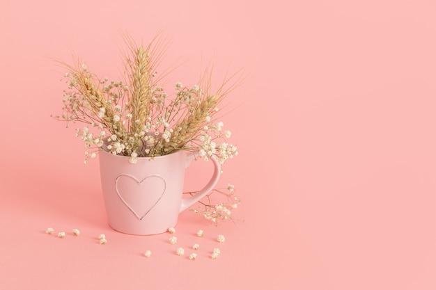 Épis de blé dans un verre rose sur une surface rose