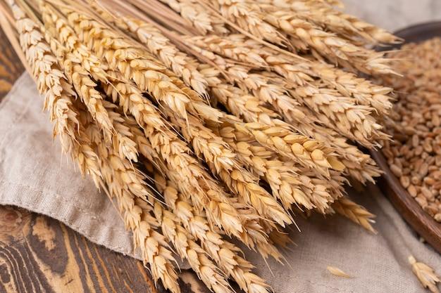 Épis de blé sur une vieille table en bois fissurée et couverture en lin gerbe de blé sur fond vintage