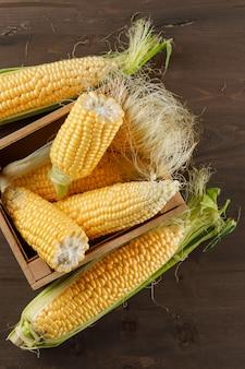 Épis de maïs dans une boîte en bois vue en plongée sur une table en bois