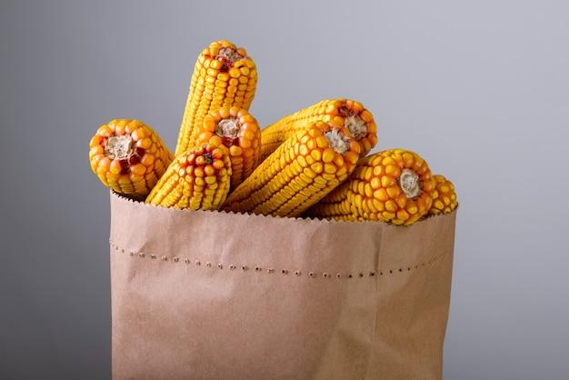 Épis de maïs dans un sac en papier sur fond gris