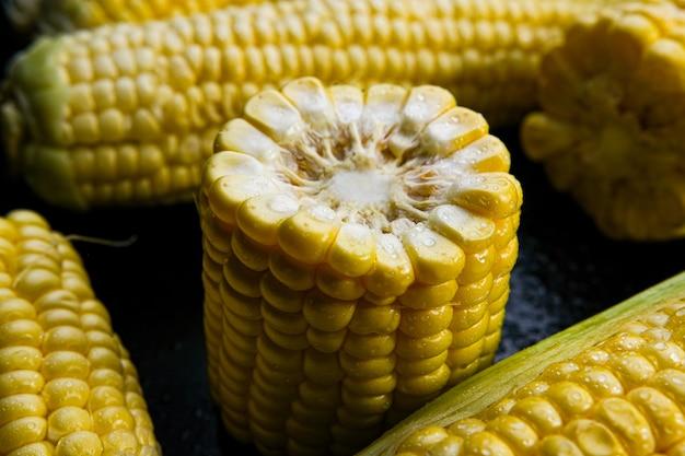 Épis de maïs doux crus frais sur fond noir. fermer.
