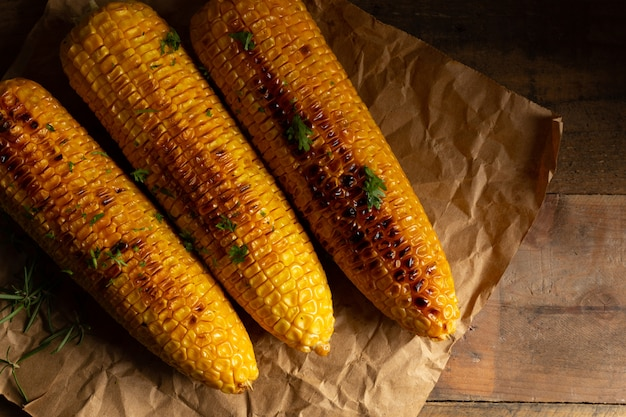 Épis de maïs grillés sur fond de bois.