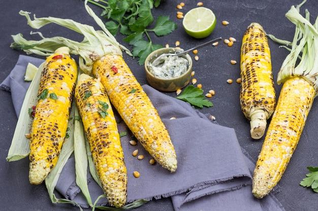 Épis de maïs grillés sur serviette grise. brins de persil et demi citron vert. bol de sauce et cuillère. fond noir. vue de dessus
