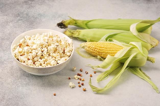 Épis de maïs et maïs soufflé préparé dans un bol sur un fond gris