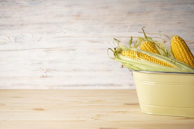 Épis de maïs mûrs dans un panier sur un fond en bois, espace pour le texte.