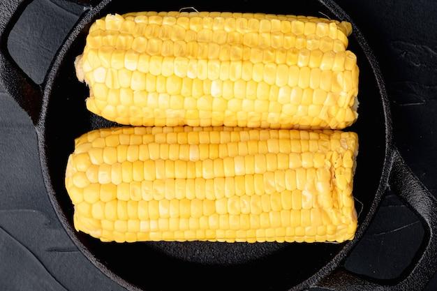 Épis de maïs sucré bouillis avec du beurre, sur fond de pierre noire, vue de dessus à plat