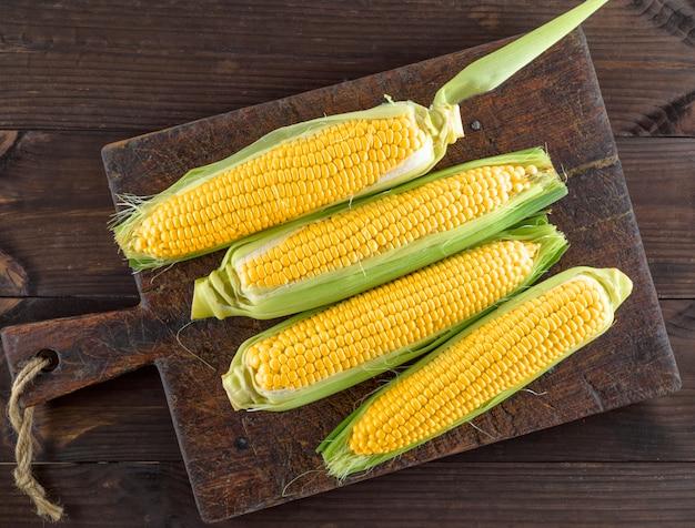 Épis de maïs sur une vieille planche de cuisine brune