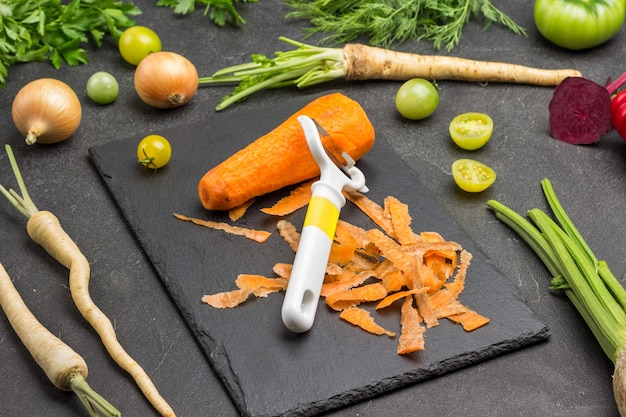 Éplucheur, carotte et épluchures sur planche à découper. racines de persil, céleri, oignons et légumes verts sur table. fond noir. vue de dessus