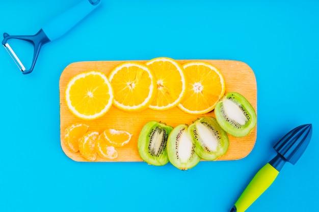 Éplucheur et presse-agrumes à la main avec des oranges et des tranches de kiwi sur une planche à découper sur fond bleu