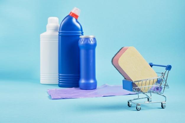 Éponge sur le chariot et ensemble de nettoyage sur les bouteilles de détergent de l'espace de copie d'arrière-plan sur fond bleu