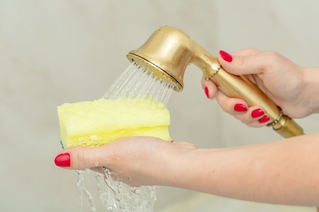 Éponge jaune dans une main féminine