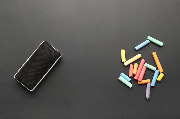 Éponge et morceaux de craie sur tableau noir, vue de dessus