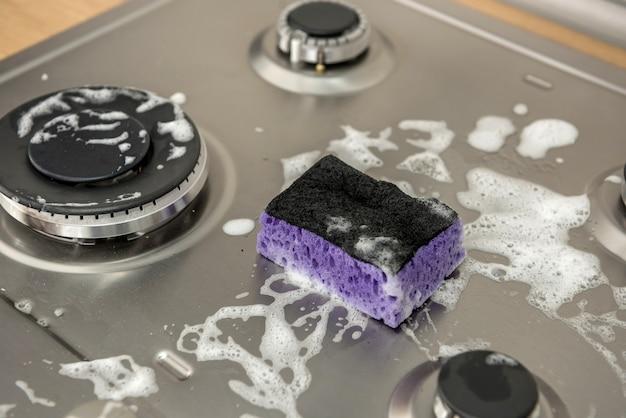 Éponge avec de la mousse sur la cuisinière à gaz sale pour le nettoyage. une maison propre est un mode de vie sain