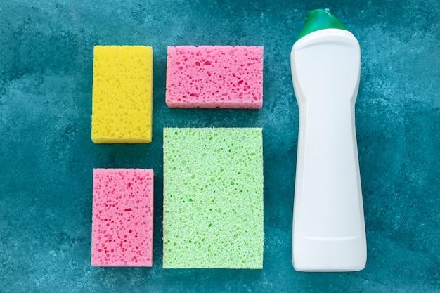 Éponges de cuisine et nettoyant antibactérien en bouteille, concept de désinfection. ménage, travaux ménagers. éponges colorées pour laver la vaisselle et nettoyer