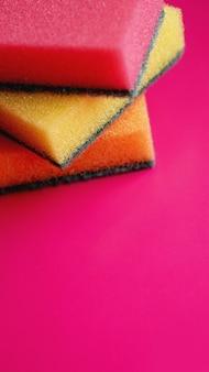 Éponges - gros plan. concept de nettoyage domestique. éponges jaunes roses orange colorées sur fond rose, mise au point douce, texte de copie.