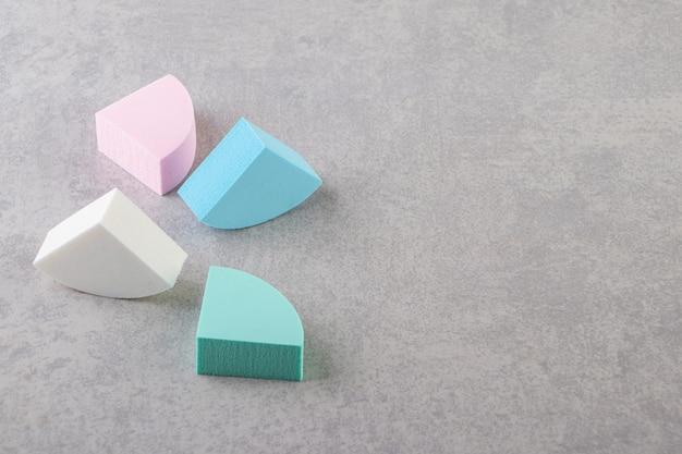 Éponges de maquillage colorées placées sur une table en pierre.