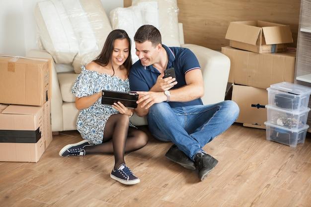 Épouse et mari s'occupant des meubles sur leur tablette. beau jeune couple