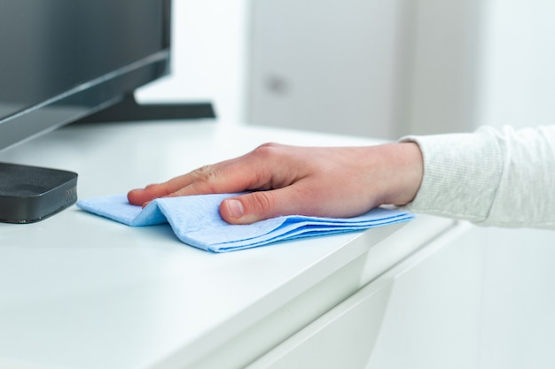 Épousseter et nettoyer les meubles avec un chiffon à la maison. entretien ménager et tâches ménagères