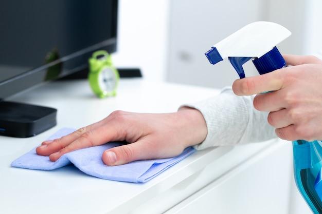Épousseter et nettoyer les meubles avec un chiffon et un spray à la maison. ménage et tâches ménagères. maison propre, propreté