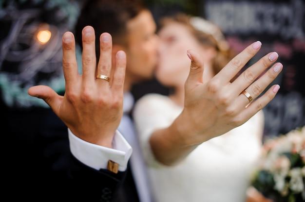 Époux et épouse s'embrassant et montrant des anneaux de mariage sur leurs doigts