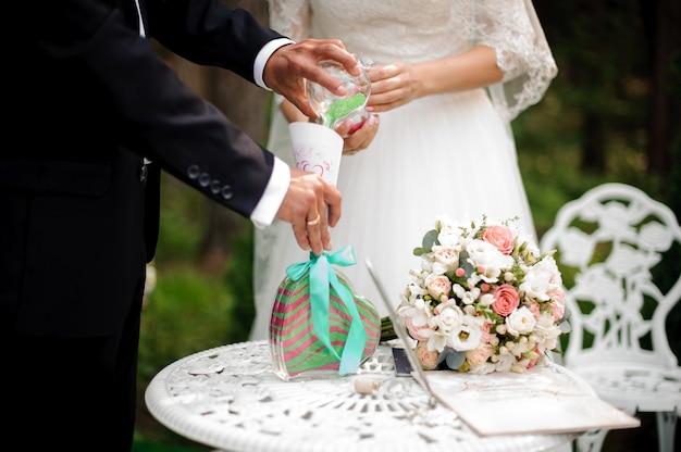 Époux avec mariée versant du sable multicolore