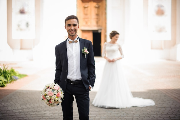 Époux tenant un bouquet de mariée et souriant