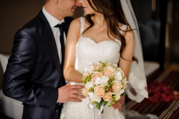 L'époux va embrasser la charmante mariée avec un bouquet